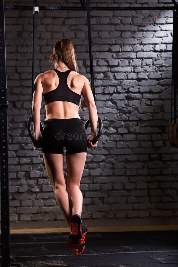 Foto der hinteren Ansicht der schönen weiblichen sportlichen Frau, die Ringausrüstung in der geeigneten Turnhalle des Kreuzes geg lizenzfreies stockbild
