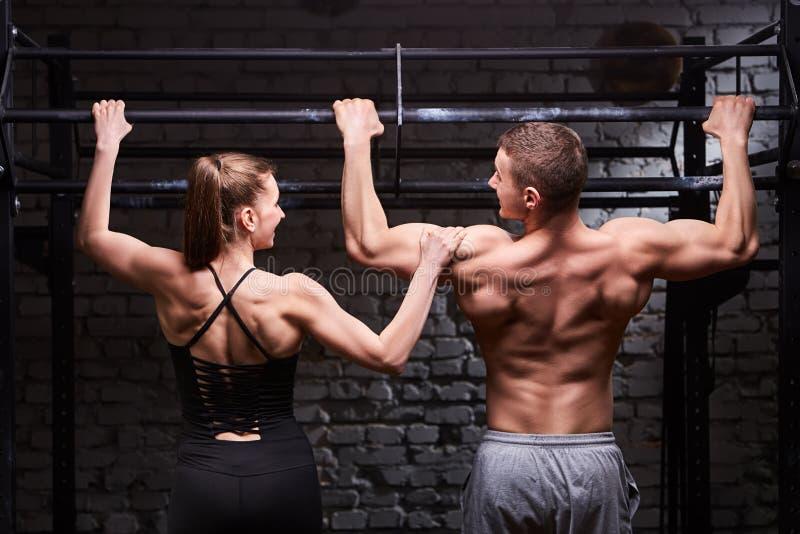 Foto der hinteren Ansicht von Paaren des Mannes und der Frau im sportwear, das Übung auf einer horizontalen Stange gegen Backstei stockfoto