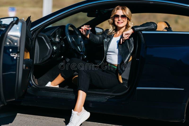 Foto der jungen Blondine mit den Schlüsseln, die im Auto mit offener Tür sitzen stockfotos