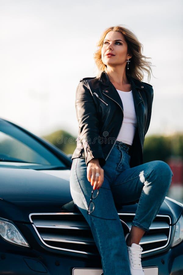 Foto der jungen Blondine mit Gläsern in den Händen, die auf Haube des schwarzen Autos sitzen stockfoto