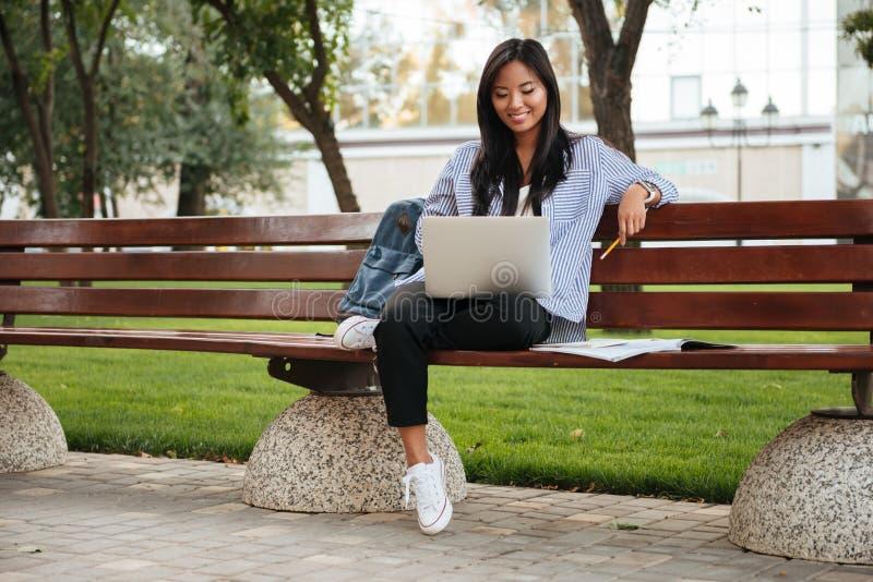 Foto der jungen glücklichen asiatischen Studentin, die mit Laptop sich entspannt, stockbilder
