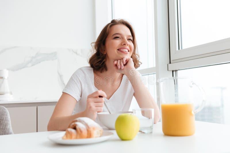 Foto der jungen lächelnden Brunettefrau im weißen T-Shirt, das hea hat lizenzfreie stockfotografie