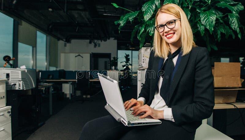 Foto der lächelnden Frau in den Gläsern mit Laptop lizenzfreie stockfotografie