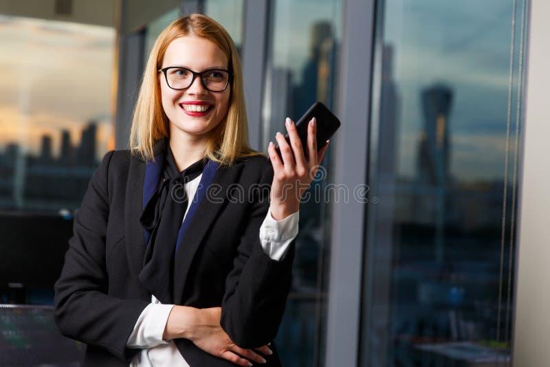 Foto der lächelnden Frau in den Gläsern mit Telefon in den Händen nahe Glaswand stockbilder