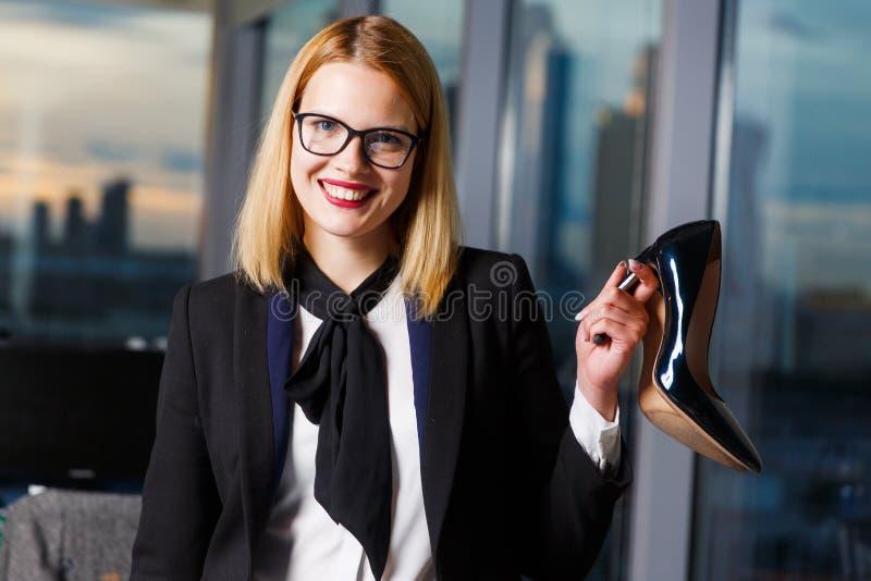 Foto der lächelnden Frau mit Gläsern mit Schuh in den Händen stockbild