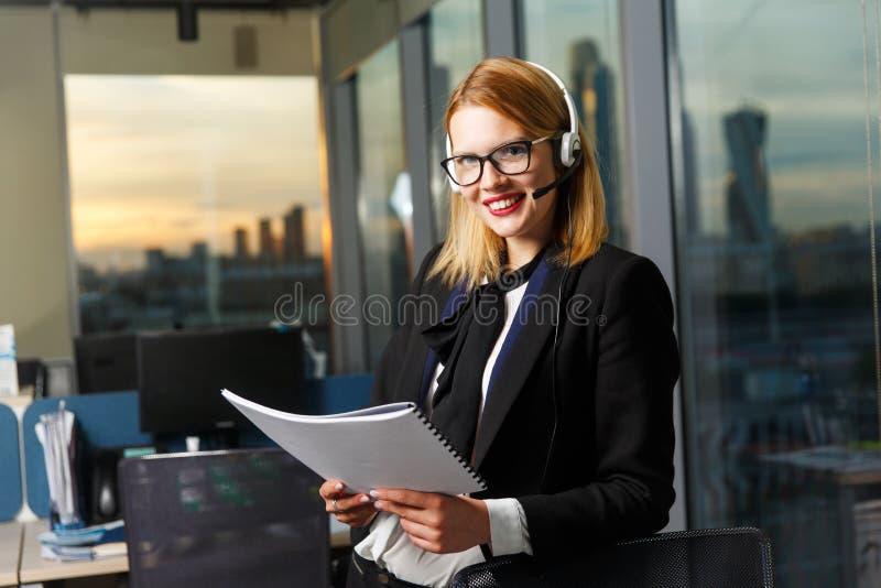 Foto der lächelnden Frau mit Gläsern und Kopfhörern mit Papier in den Händen nahe Glaswand lizenzfreie stockfotos