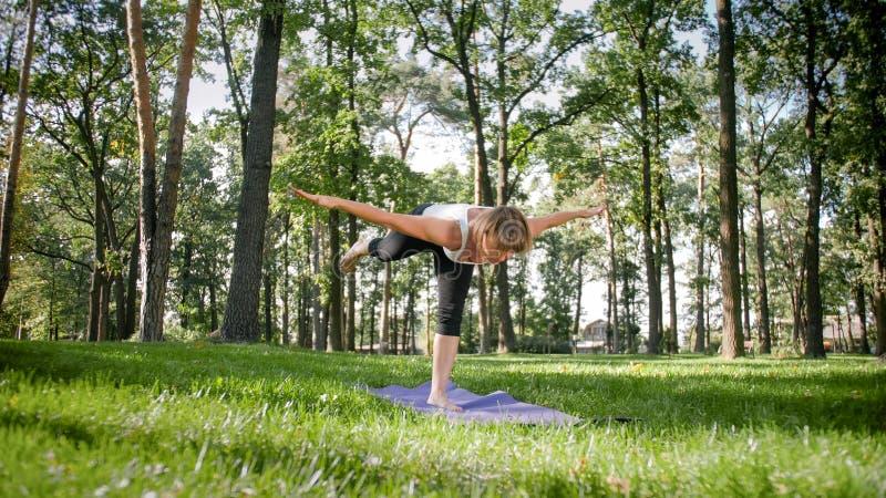 Foto der l?chelnden Frau Yoga- und Eignungs?bungen tuend Mittlere gealterte Leute, die um ihrer Gesundheit sich k?mmern Harmonie  stockbild
