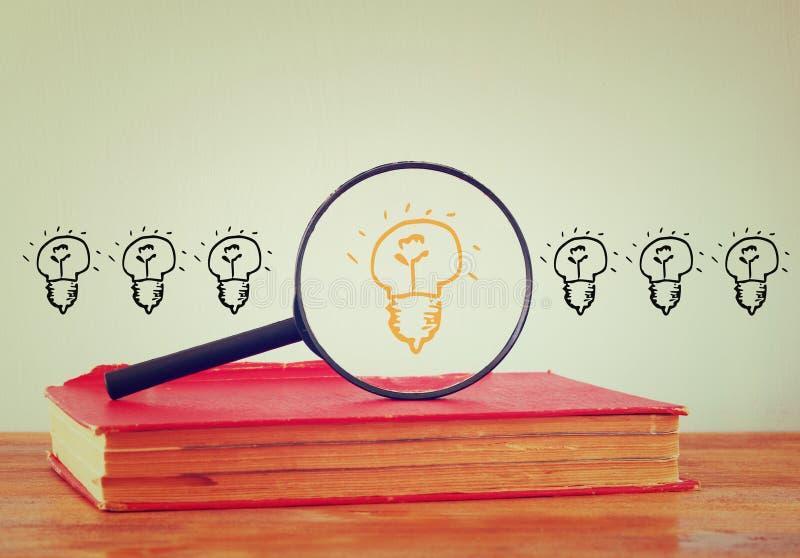 Foto der Lupe suchend nach einer Glühlampe der guten Idee Bild wird gefiltert lizenzfreie abbildung