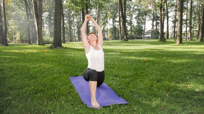 Foto der Mitte alterte lächelndes übendes asana Yoga der Frau Persong, der in der Natur meditiert Balance und Harmonie des Körper lizenzfreies stockfoto