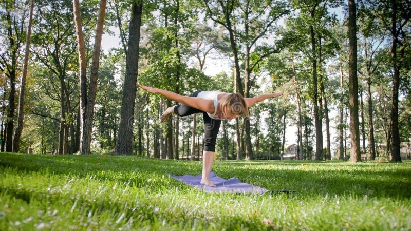 Foto der Mitte alterte l?chelndes ?bendes asana Yoga der Frau Persong, der in der Natur meditiert Balance und Harmonie des K?rper lizenzfreie stockfotografie