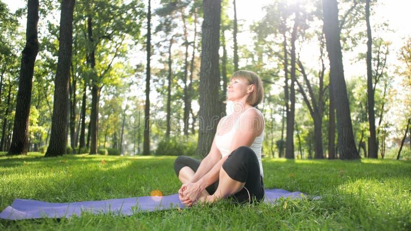 Foto der Mitte alterte l?chelndes ?bendes asana Yoga der Frau Persong, der in der Natur meditiert Balance und Harmonie des K?rper stockbild