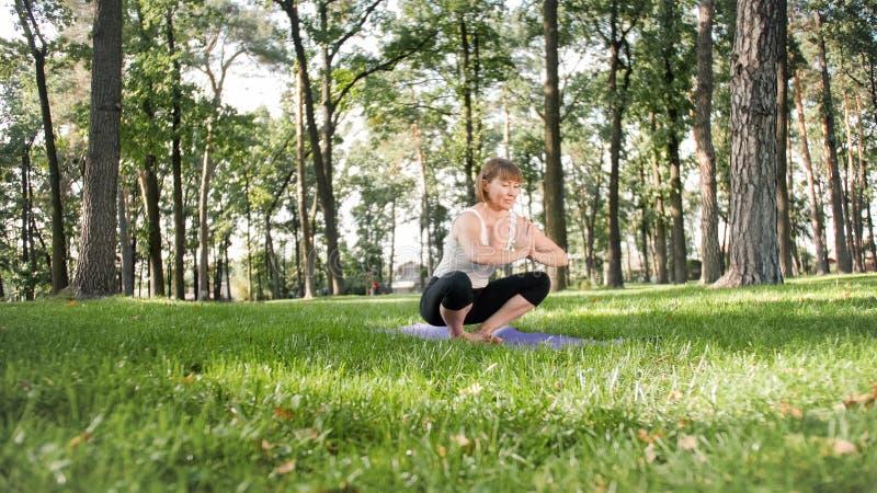 Foto der Mitte alterte l?chelndes ?bendes asana Yoga der Frau Persong, der in der Natur meditiert Balance und Harmonie des K?rper stockfotografie
