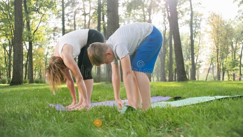 Foto der mittleren Greisin ihren Studenten in der Yogaklasse am Park unterrichtend Woamn mit ?bender Eignung des Teenagers lizenzfreie stockfotos