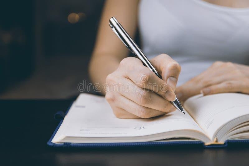 Foto der Person schreibend auf Notizbuch lizenzfreies stockbild