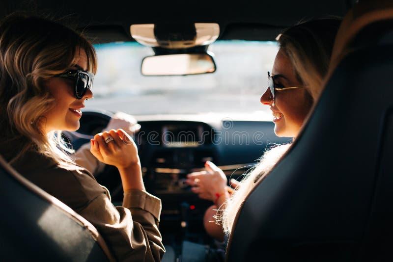 Foto der Rückseite von zwei jungen Frauen, die im Auto am vorderen Sitz sitzen lizenzfreies stockfoto