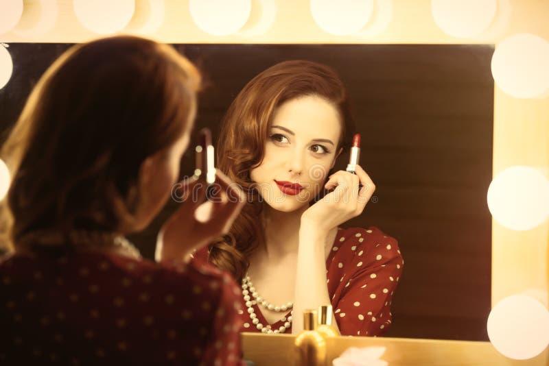 Foto der schönen jungen Frau, die ihren Lippenstift nahe dem Gewinn hält stockbild