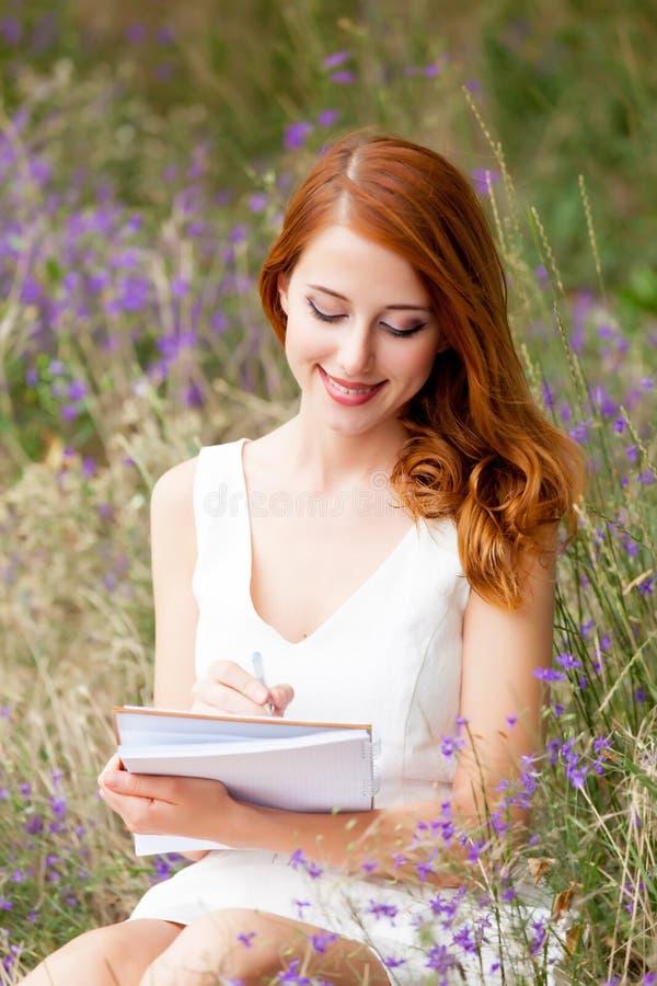 Foto der schönen jungen Frau mit dem Schreibheft, das auf den gras sitzt lizenzfreie stockfotos