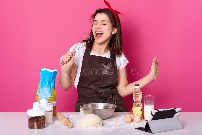 Foto der Schönheit Kuchen machend Dame steht über rosafarbener Wand, hält Schneebesen als Mikrofon und singt Lieder, hörende Musi lizenzfreie stockbilder