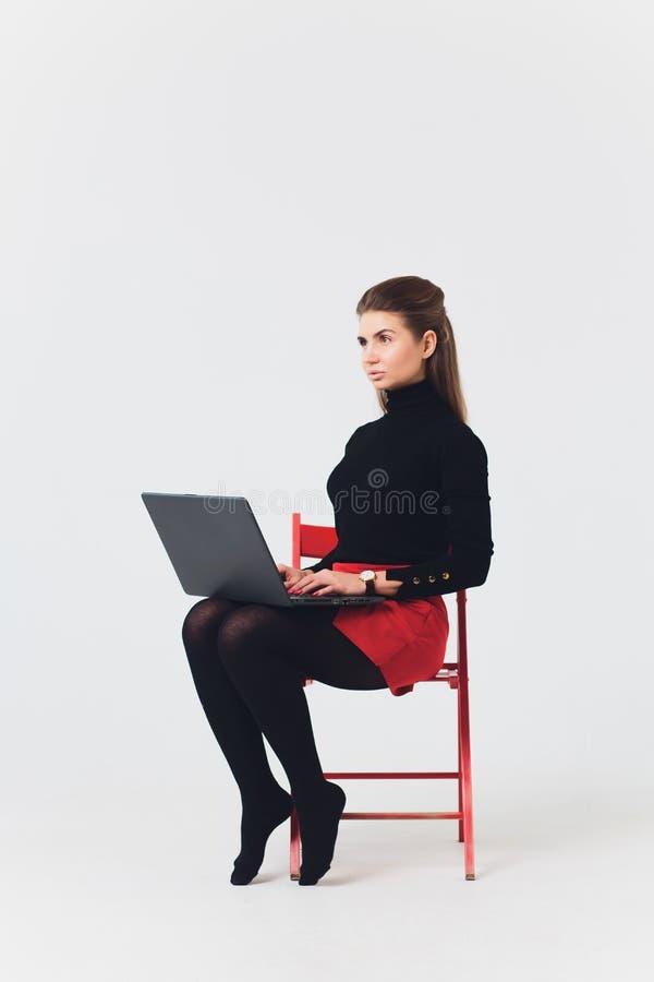 Foto der Schönheit 20s, die Computer mit den Beinen lächelt und verwendet, kreuzte lokalisiert über weißem Hintergrund stockfotografie