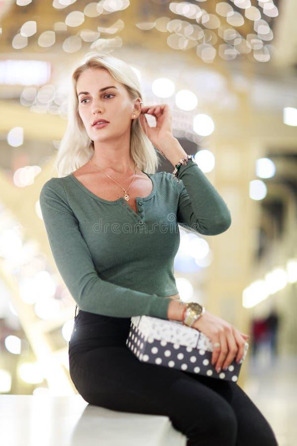 Foto der sitzenden Blondine mit Geschenkbox lizenzfreie stockfotografie