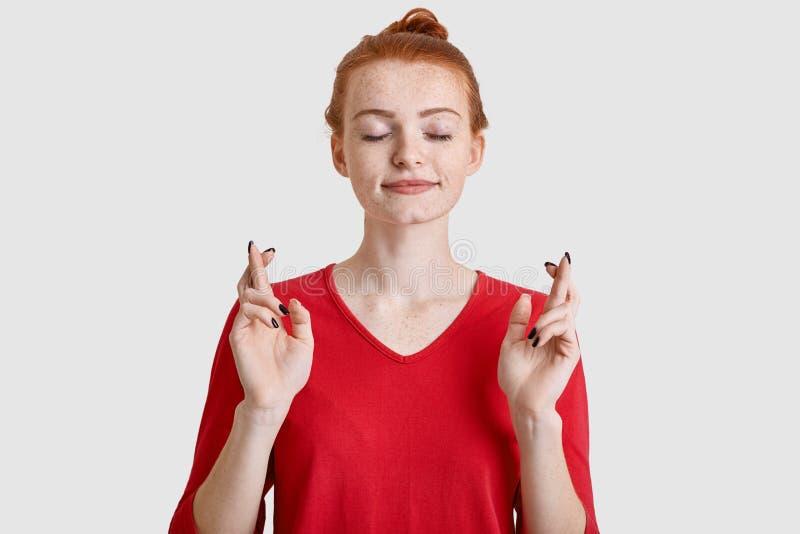 Foto der sommersprossigen jungen Frau mit minimalem bilden, haben das Ingwerhaar, das im Knoten gekämmt wird, kreuzt die Finger f lizenzfreie stockbilder