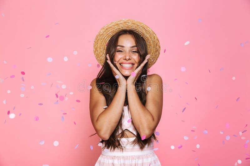 Foto des überraschten Weilestands des Strohhutes der Frau 20s tragenden lachenden lizenzfreies stockfoto