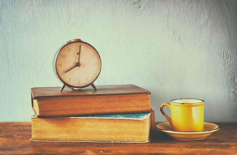 Foto des alten Weckers über Holztisch, mit verblaßtem Retro- Effekt stockfoto