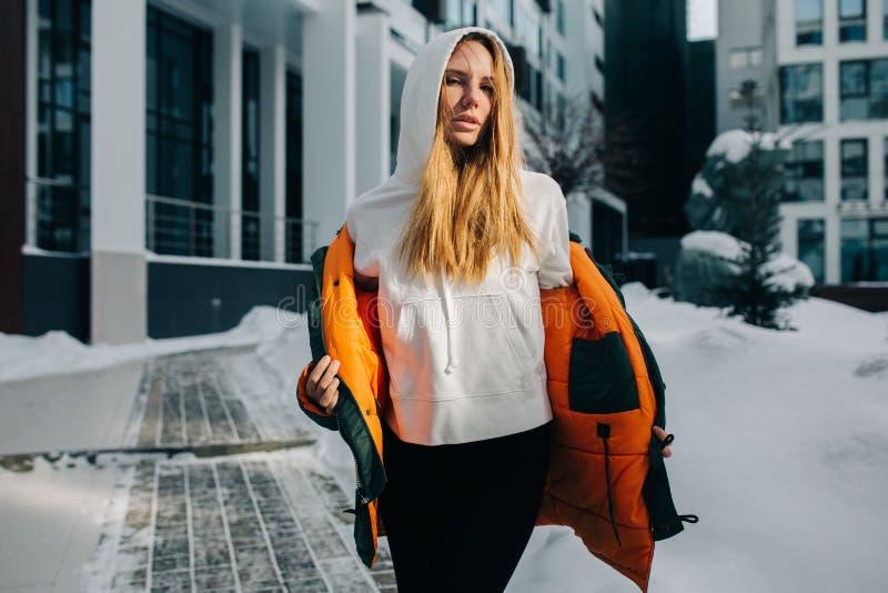 Foto des blonden Mädchens in der Haube und in der Jacke gegen Wintertag stockbild
