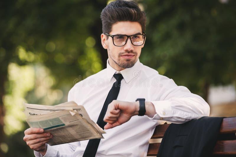 Foto des ernsten Geschäftsmannes in der Klagenlesezeitung auf Bank lizenzfreie stockfotos