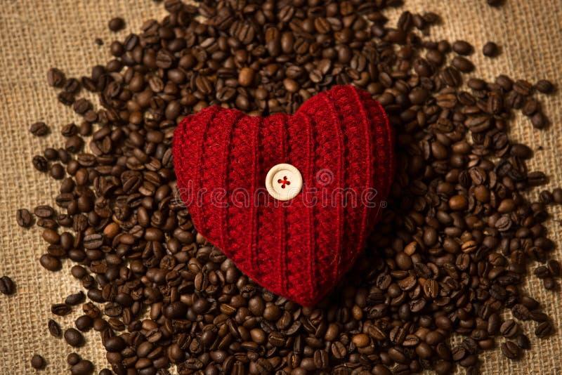 Foto des gestrickten roten Herzens, das auf Stapel von Kaffeebohnen liegt lizenzfreie stockfotos