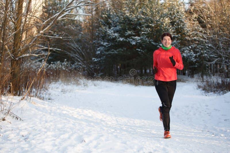 Foto des glücklichen Sportmädchens auf Morgen laufen in Winterpark lizenzfreies stockbild