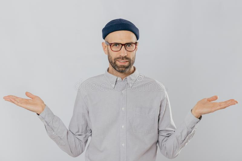 Foto des gut aussehenden Mannes mit unsicherem Ausdruck, verbreitet Hände, trägt die Gläser und Kopfbedeckung, lokalisiert über w lizenzfreie stockfotografie