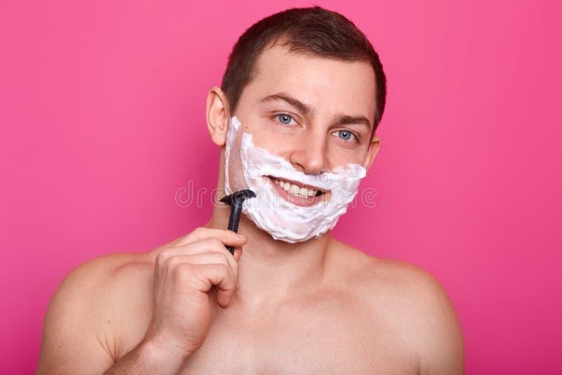 Foto des hemdlosen jungen Mannes, der sein Gesicht rasiert und Kamera bei der Stellung auf rosa Hintergrund, Aufstellung nackt mi stockfotografie