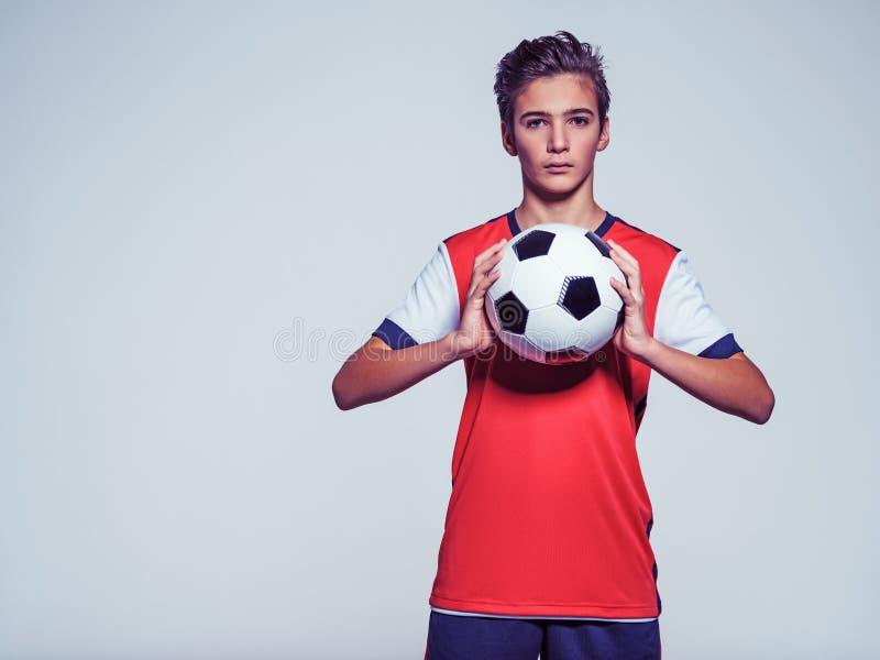 Foto des jugendlich Jungen in der Sportkleidung, die Fußball hält stockbilder