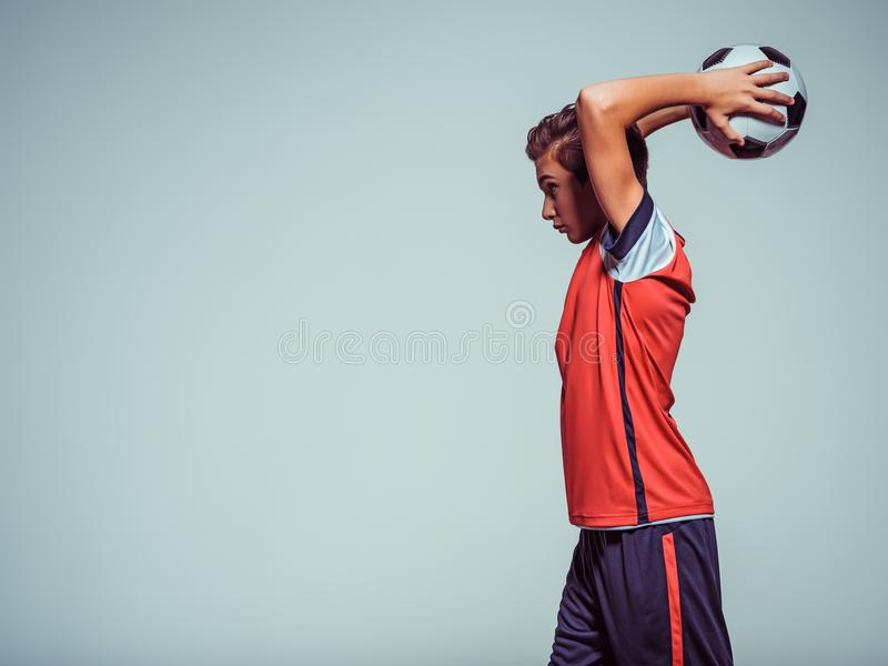 Foto des jugendlich Jungen in der Sportkleidung, die Fußball hält lizenzfreies stockbild