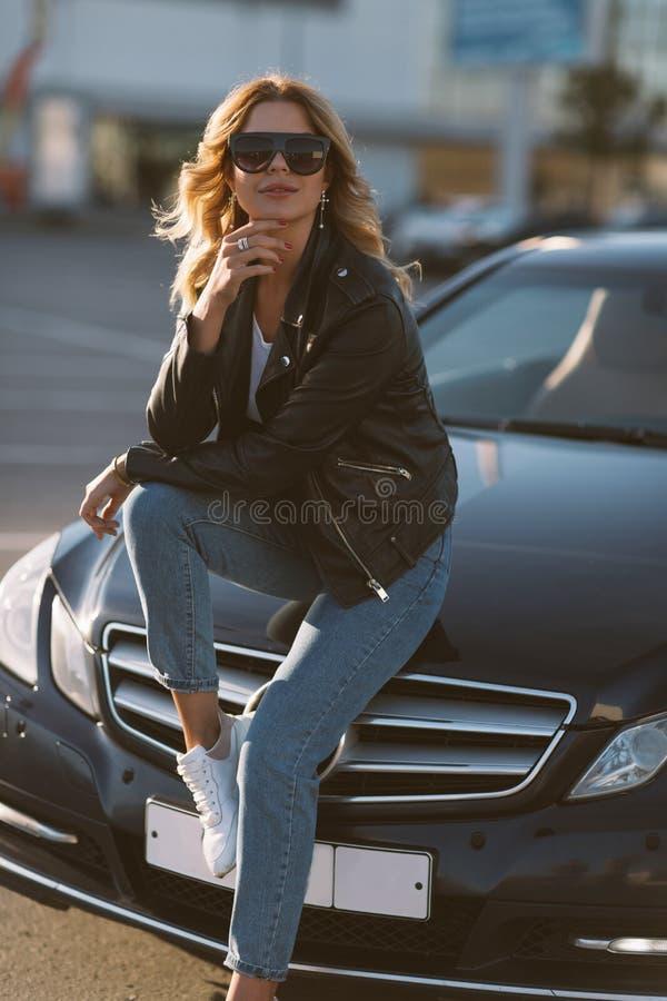 Foto des jungen blonden Mädchens in der Sonnenbrille, die auf Haube des schwarzen Autos sitzt stockfotografie
