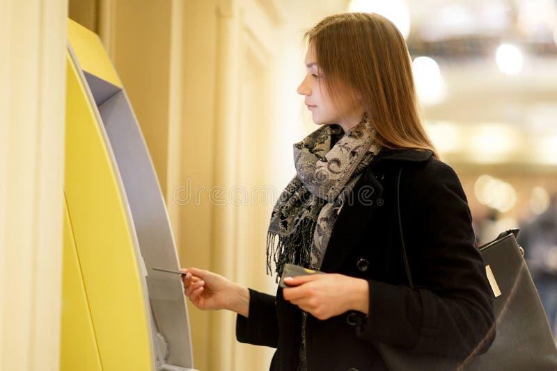Foto des jungen Brunette mit Bankkarte an ATM auf unscharfem Hintergrund stockfoto