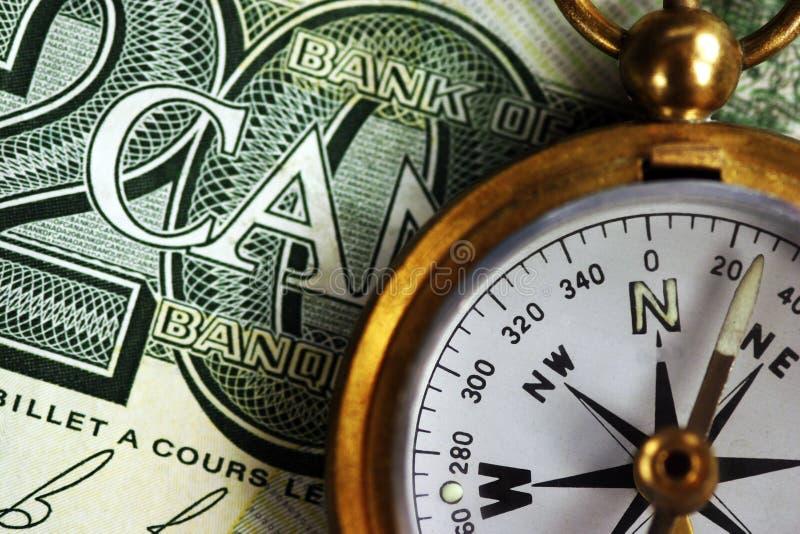 Foto des kanadischen Geldes und des Messing-Kompassses stockbild