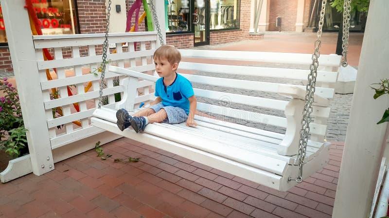 Foto des kleinen Kleinkindjungen, der auf weißer hölzerner Schwingenbank auf alter europäischer Stadtstraße sitzt lizenzfreie stockbilder