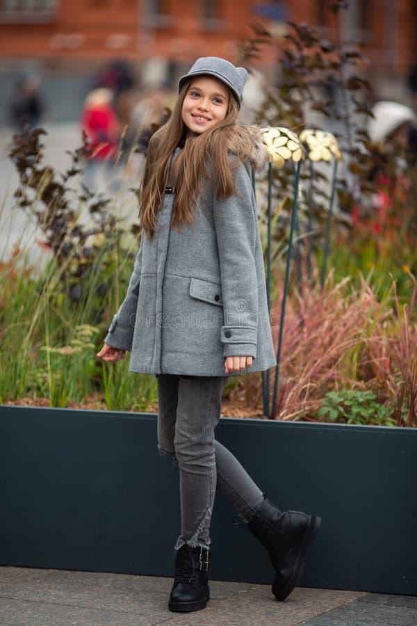 Foto des lächelnden Mädchens im grauen Hut und im Mantel stockfoto