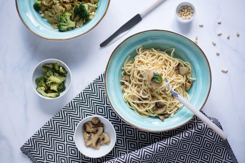 Foto des Lebensmittels eine Platte von Teigwaren mit Pilzen, Brokkoli, Sonnenblumensamen des indischen Sesams, Geschirr stockfoto