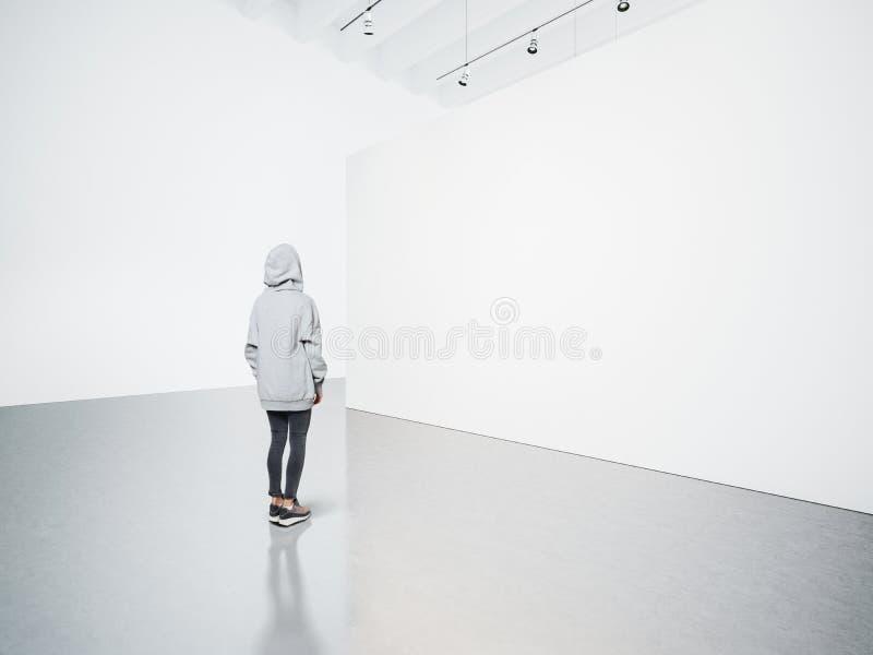 Foto des Mädchens in der modernen Galerie, die das leere Segeltuch betrachtet stockfotos