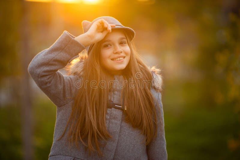 Foto des Mädchens im grauen Hut und im Mantel auf unscharfem Hintergrund an der Stadt lizenzfreies stockbild