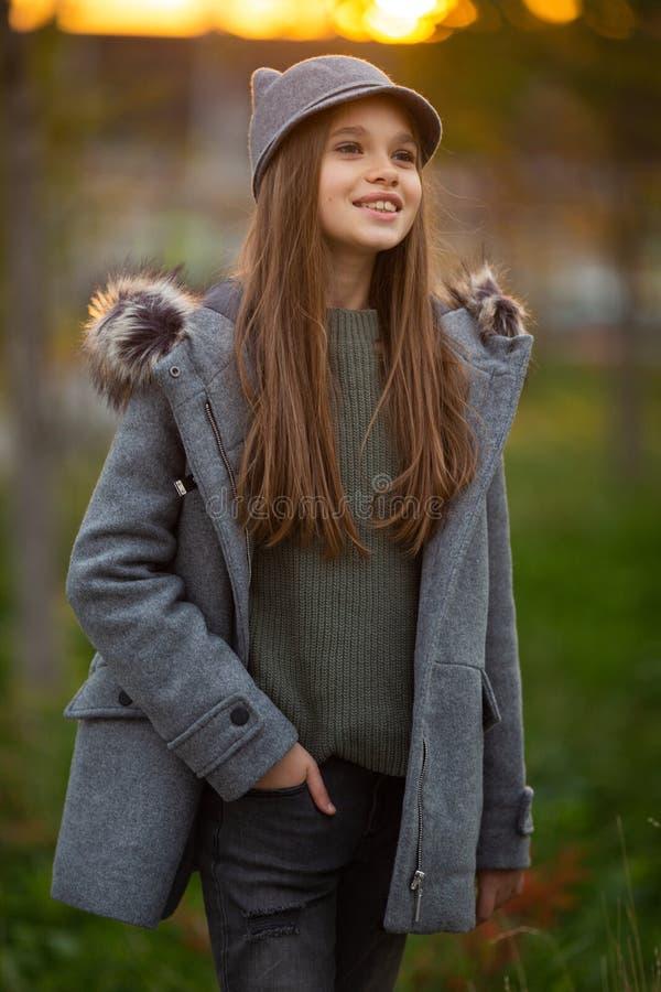 Foto des Mädchens im grauen Hut und im Mantel auf unscharfem Hintergrund an der Stadt lizenzfreie stockbilder