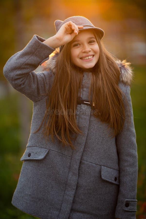 Foto des Mädchens im grauen Hut und im Mantel auf unscharfem Hintergrund an der Stadt lizenzfreie stockfotografie