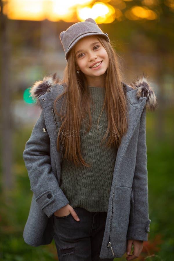 Foto des Mädchens im grauen Hut und im Mantel auf unscharfem Hintergrund an der Stadt stockfoto