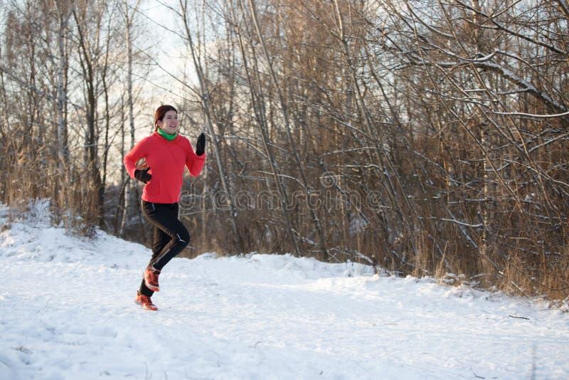 Foto des Mädchens im Sport, der auf Morgen einheitlich ist, laufen in Winterwald lizenzfreies stockbild