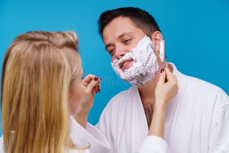 Foto des Mädchens Mann im weißen Mantel rasierend stockfotografie