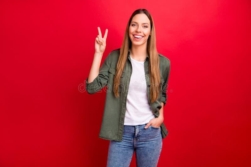 Foto des netten netten genießenden überglücklichen Mädchens, das Ihnen Vzeichenholdinghand in der Tasche zeigt, während Sie mit R lizenzfreies stockbild