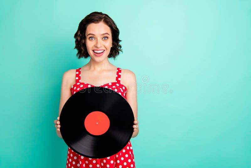 Foto des reizend schönen aufgeregten genießenden Mädchens, das ihre Großväter alte vynil Platte gefunden wird, während Sie mit Kn stockfoto
